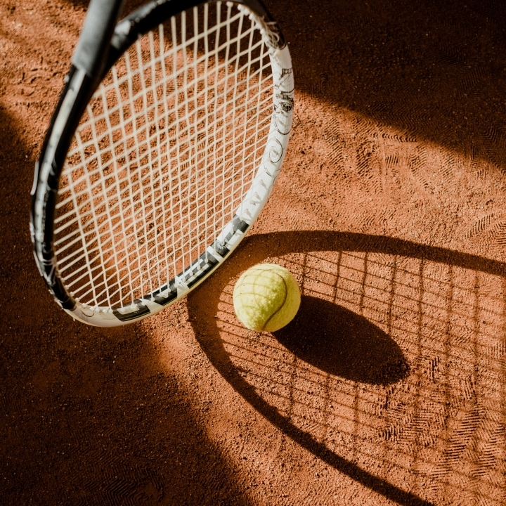 Tennis racket and ball in shadow