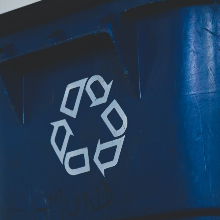 Close-up of a recycling logo on a bin
